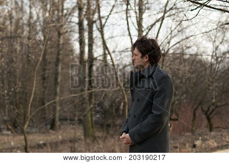Portrait of a young handsome man sad looking to the left in the park, the woods in autumn or spring. Portrait on the nature of the park, the woods, on the street, horizontal picture. Real people series