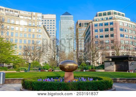 London UK - May 24 2017 - 'Cosmic Stone' by Do Vassilakis-Koning in a peaceful garden at Westferry Circus in Canary Wharf with skyscrapers in the background