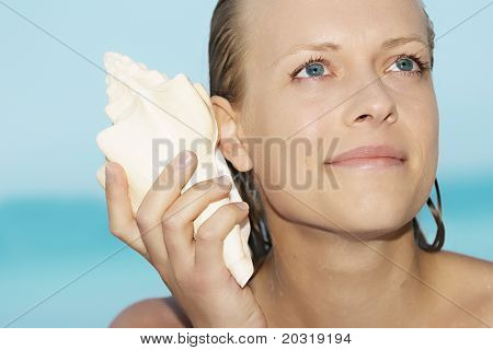 woman with shell to her ear