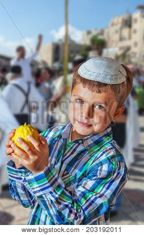Beautiful Jewish boy with green eyes, in a white skullcap, with citrus in his hand. Autumn Jewish holiday Sukkot. Jerusalem, Israel
