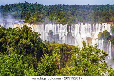 Waterfalls of the Brazilian national park Iguazu. Iguazu Falls. Boiling water creates a watery dust and a rainbow. The concept of ecological and extreme tourism