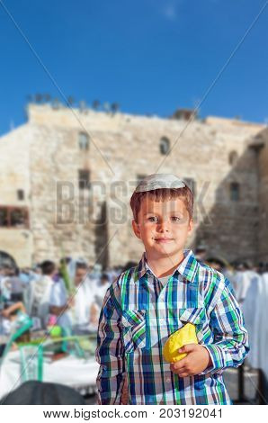 Beautiful Jewish boy with green eyes, in a skullcap, with citrus in his hand. Autumn Jewish holiday Sukkot. The shrine of Judaism is the Western Wall of the Temple