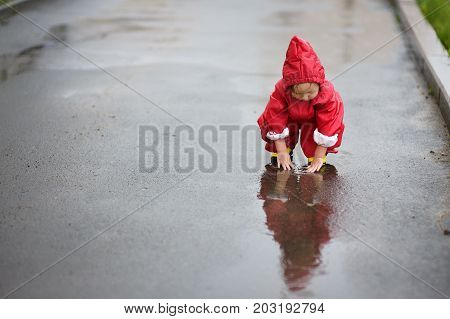 The child plays in pools in the rain