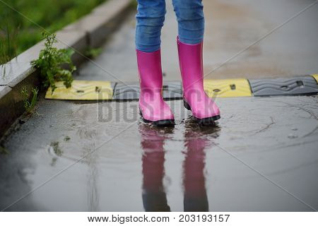 the child's legs in gumboots walk on pools in the rain