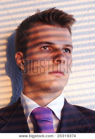young businessman looking out of the office window, shadows from blinds on his face