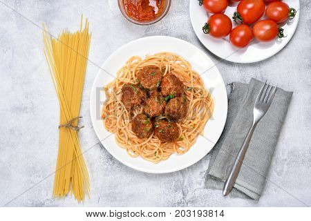 Spaghetti with tomato sauce and meatballs on light background top view