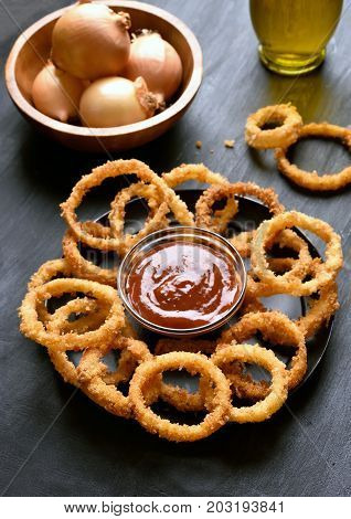 Fried onion rings and ketchup on dark background