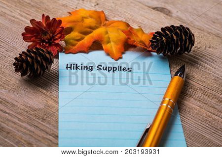 Fall Hiking Supplies list concept on notebook and wooden board