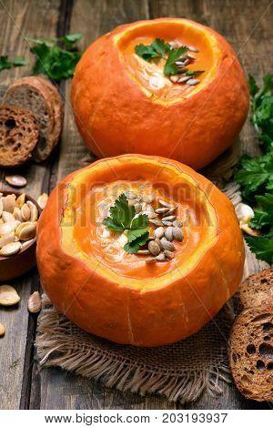Vegetarian vegetable pumpkin soup on wooden table. Healthy diet food
