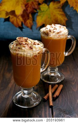 Pumpkin latte with whipped cream and cinnamon on wooden table