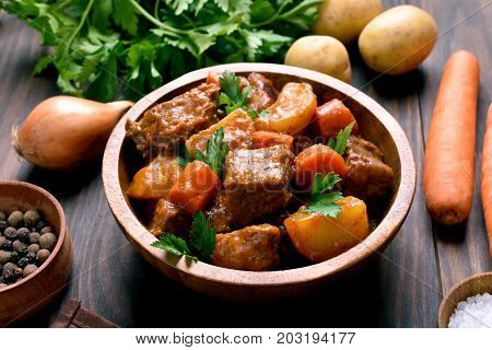 Dish for dinner. Meat stew with vegetables in wooden bowl