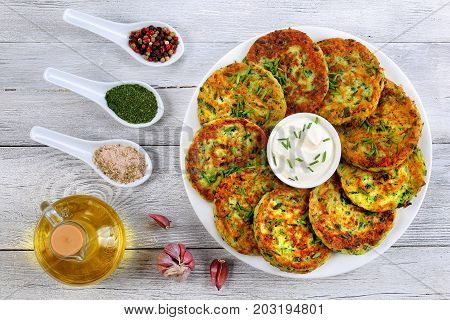 delicious zucchini fritters on white plate with sour cream in centre of dish sprinkled with finely chopped chives spices. bottle of olive oil on wooden table vegetarian recipe view from above