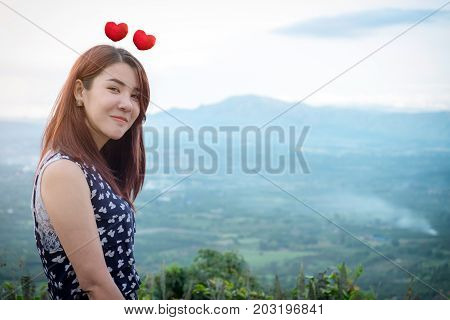 Valentine's Day love and feelings Young Asian beautiful woman smiling and in love View the scenery on mountain nature view background.