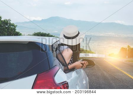 Relaxed happy traveler Young beatiful asian gilr wearing white Hat weave using smart phone and Reach out of the car at sunset and beautiful view with mountain road background.