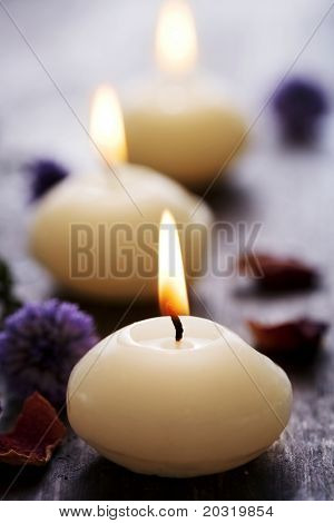 row of scented candles on wooden surfface, sorrounded by dried flowers, focus is on the front flame