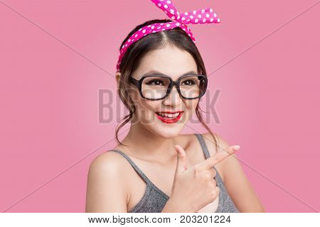 Portrait Of Asian Girl With Pretty Smile In Pinup Style Pointing On Pink Background