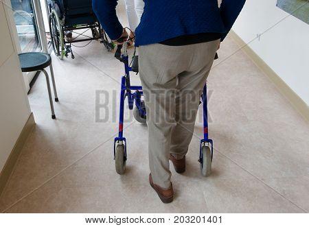 An elderly man walking behind his walking frame