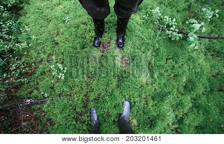 Male and female feet in rubber boots in thick moss.