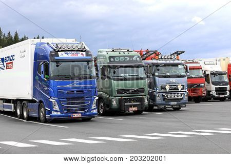 FORSSA FINLAND - AUGUST 25 2017: Colorful Volvo trucks parked on the asphalt yard of a truck stop on a cloudy day.