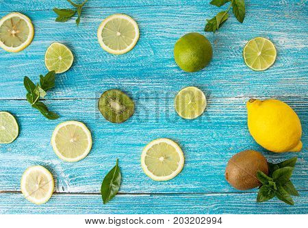 Flat Lay Still Life With Mint, Kiwi, Lemon And Lime On Blue Background. Slices Of Citrus And Kiwi.