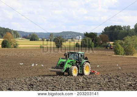 SALO FINLAND - AUGUST 20 2017: Farmers cultivate field with two John Deere tractors and Kverneland harrows on a beautiful day of early autumn.