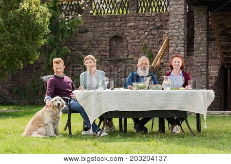 smiling family sitting at table together during dinner at countryside