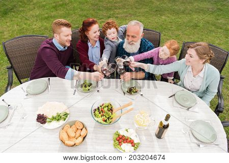 high angle view of cheerful family clinking glasses while having dinner together