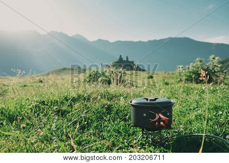 Cooking in the mountain hike on a gas burner in a bowler hat against the backdrop of the mountains sunset against the backdrop of the Trinity Church Georgia Caucasus Mountains Kazbek
