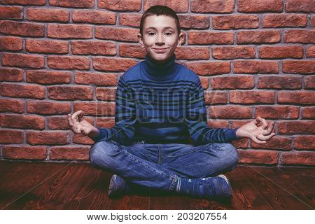 Portrait of a smiling nine year old boy sitting on a floor like yoga.