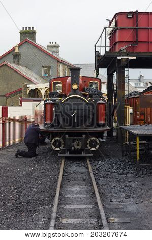 Porthmadog Wales UK - September 4 2017: Narrow gauge steam locomotive David Lloyd George of the Ffestiniog Railway Company having maintenance performed at the coaling station in Porthmadog