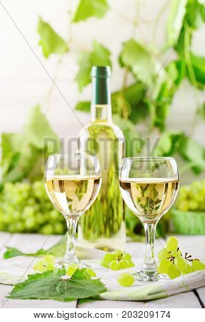 Glasses with white wine, fresh grapes and a bottle of white wine on white wooden table.