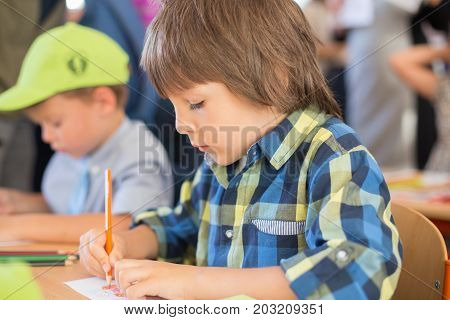Young First Grade Student Sitting At Desk On His First Day At School