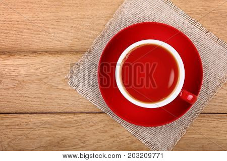 Full Cup Of Black Tea In Red Cup On Wooden Table