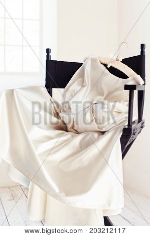Soft white new wedding dress on black chair. Indoors vertical image.