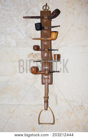 collection of pipes hanging on the wall on a horse stirrup strap