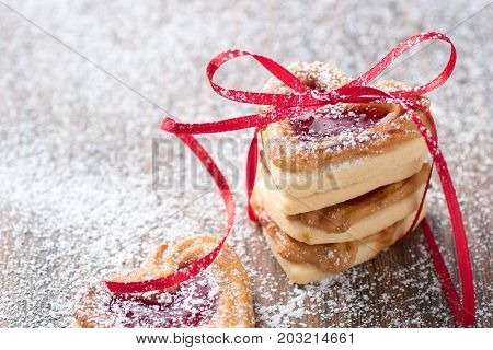 Fresh jam filled heart cookies with icing sugar and ribbon on a rustic wodden table. Ise it for a recipe or greeting card
