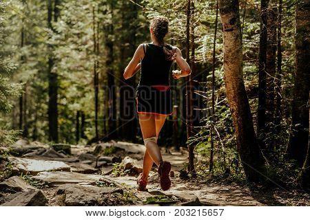 girl runner running trail stone in forest in knee pads