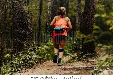 woman runner in knee pad running trail forest