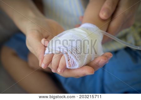 Mother Holding Child's Hand Receiving Iv Saline Solution In Hospital.