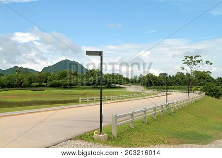 Curved road with white picket fence and blue cloudy sky in farmland