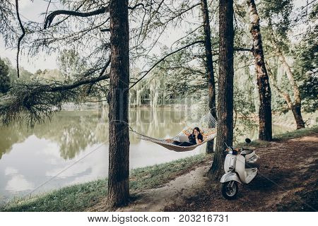 Girl Working On Laptop While Lying On Hammock In Sunny Summer Park. Freelancer Woman Hipster With La