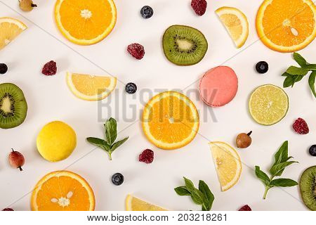 Flat Lay Still Life With Macarons, Berries, Mint And Citrus And Other Fruits