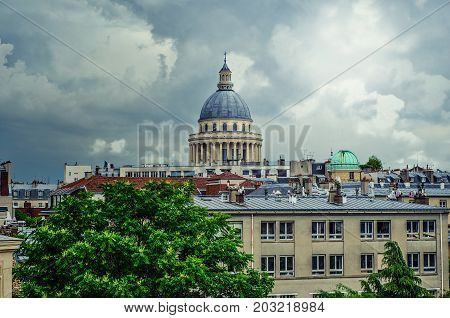 Paris,  France - June 2, 2017: Pantheon cupola with a dome over colonnade of columns and building of Institute Curie are seen in the overcast background