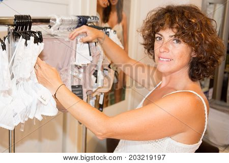 Attractive Curly Woman Shopping For Underwear In Clothing Store