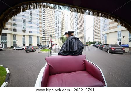 Coachman are on trestles of couch and horse near residential buildings, back view from couch
