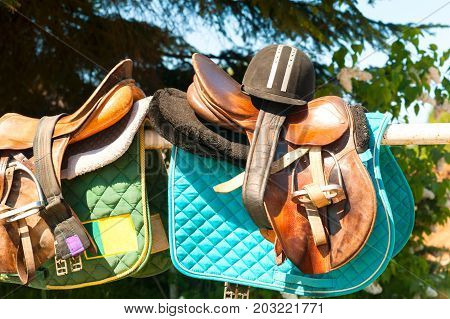 Equestrian sport equipment and accessories hanging on metal fence. Vibrant colored summertime outdoors horizontal image.