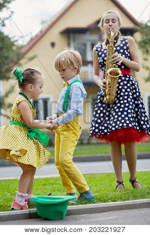 Teenage girl plays saxophone and little boy and girl in dancing suits dance on grassy lawn against two-storied house near road, hat for earnings on the road.