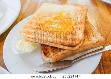 Bread toast with orange jam cream and the knife steel serve on white dish for food background.