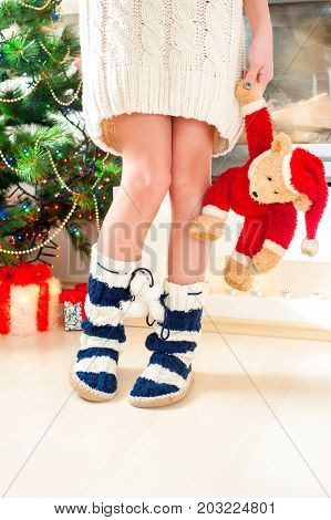 Teenage girl in cozy warm knitted woolen blue socks with pompons holding christmas teddy bear toy. Multicolored indoors vertical image.