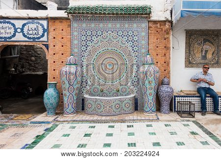 Fez Morocco - May 07 2017: Moroccan factory worker of the Mosaic Factory in Fez is sitting on a bench smoking a cigarette in the courtyard next to a beautiful mosaic fountain while having a break.